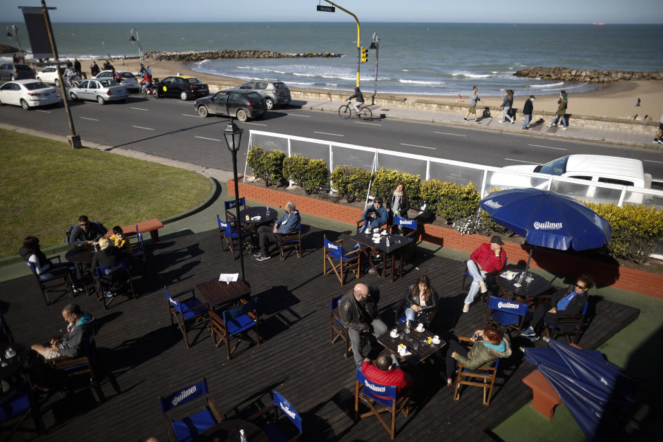 People sit outside at a restaurant during the COVID-19 pandemic in Mar del Plata, Argentina, Saturday, Oct. 10, 2020. Mar del Plata, which at the start of the pandemic reported one case a day or less, is now reporting an average of 300 confirmed coronavirus cases a day. (AP Photo/Natacha Pisarenko)