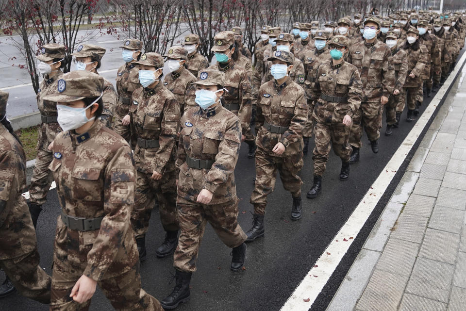 In this Jan. 26, 2020, photo released by Xinhua News Agency, members of a military medical team head for Wuhan Jinyintan Hospital in Wuhan, central China's Hubei province. China on Monday expanded sweeping efforts to contain a viral disease by postponing the end of this week's Lunar New Year holiday to keep the public at home and avoid spreading infection. (Cheng Min/Xinhua via AP)