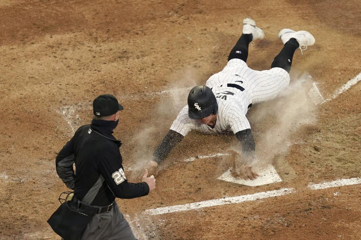Chicago White Sox's Andrew Vaughn scores off Billy Hamilton's triple as home plate umpire Sean Barber watches during the first inning of a baseball game against the Minnesota Twins Wednesday, May 12, 2021, in Chicago. (AP Photo/Charles Rex Arbogast)