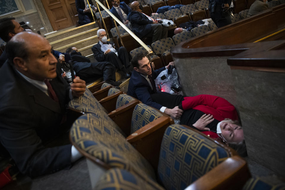 Rep. Jason Crow, D-Colo.,  comforts Rep. Susan Wild, D-Pa., while taking cover as protesters disrupt the joint session of Congress to certify the Electoral College vote on Wednesday, January 6, 2021. (Tom Williams/CQ Roll Call via Getty Images)