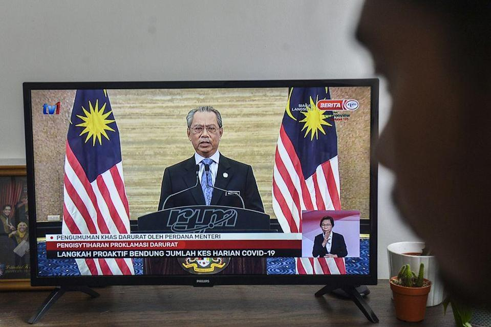 A man watches a live telecast of Prime Minister Tan Sri Muhyiddin Yassin's speech in Kuala Lumpur January 12, 2020. Muhyiddin said the government does not expect as severe an economic impact as seen with the first MCO implemented in the second quarter of 2020, as more economic activities are allowed to operate. — Picture by Miera Zulyana