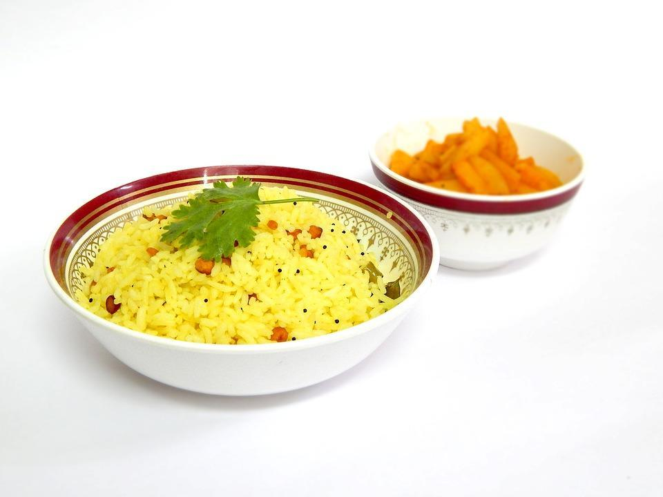 <p>Lemon rice is a favorite across homes in South of India. Easy to make, this recipe of lemon rice allows you to make a filling dish without spending too much time in your kitchen. Cook 1 cup rice in a pressure cooker & allow to cool. Heat 1 tsp oil in a kadhai & add some peanuts & fry. Remove the peanuts & reserve. Now add some mustard seeds, little bit of urad dal & chana dal to the oil. Once the mustard seeds splutter, add a few curry leaves & one dry red chili. Add little turmeric powder & add rice & mix well. Add 1-2 tsp lemon juice & salt to taste. Garnish with coriander & fried peanuts & serve hot. Image courtesy- Pixabay </p>