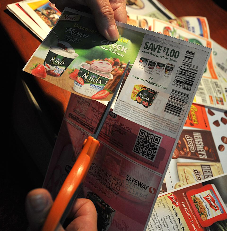 A woman cuts coupons from the advertising section of the Sunday newspaper. (Photo: KAREN BLEIER/AFP via Getty Images)
