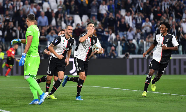 Juventus' Cristiano Ronaldo, second from right, celebrates with his teammates after scoring his side second goal on a penalty kick during the Italian Serie A soccer match between Juventus and Verona at the Juventus' Stadium in Turin, Italy, Saturday, Sept. 21, 2019. (Alessandro Di Marco/ANSA via AP)