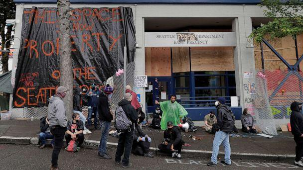 PHOTO: People sit in front of the Seattle Police Dept. East Precinct building, which has been boarded up and abandoned except for a few officers inside, June 11, 2020, in Seattle. (Ted S. Warren/AP)