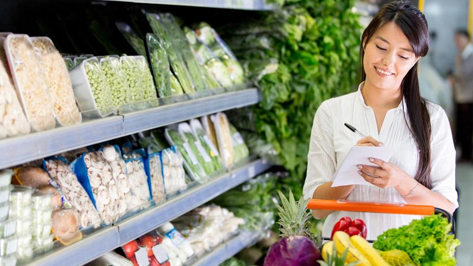 woman grocery shopping with a list