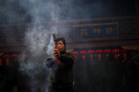 A man burns incense at the Old City God Temple in Yuyuan Garden, downtown Shanghai in this January 18, 2011 file photo. REUTERS/Carlos Barria/Files