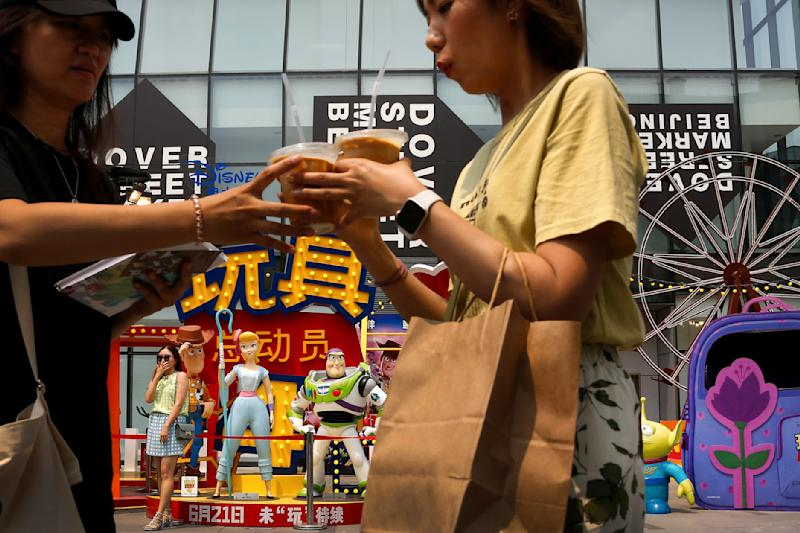 """Women stand near the American latest animated film """"Toy Story 4"""" characters on display at the capital city's popular shopping mall in Beijing, Tuesday, June 25, 2019. China says its trade negotiators are talking to their U.S. counterparts on how to resolve disputes ahead of an expected meeting between their two heads of state at the G20 meeting in Japan later this week. (AP Photo/Andy Wong)"""