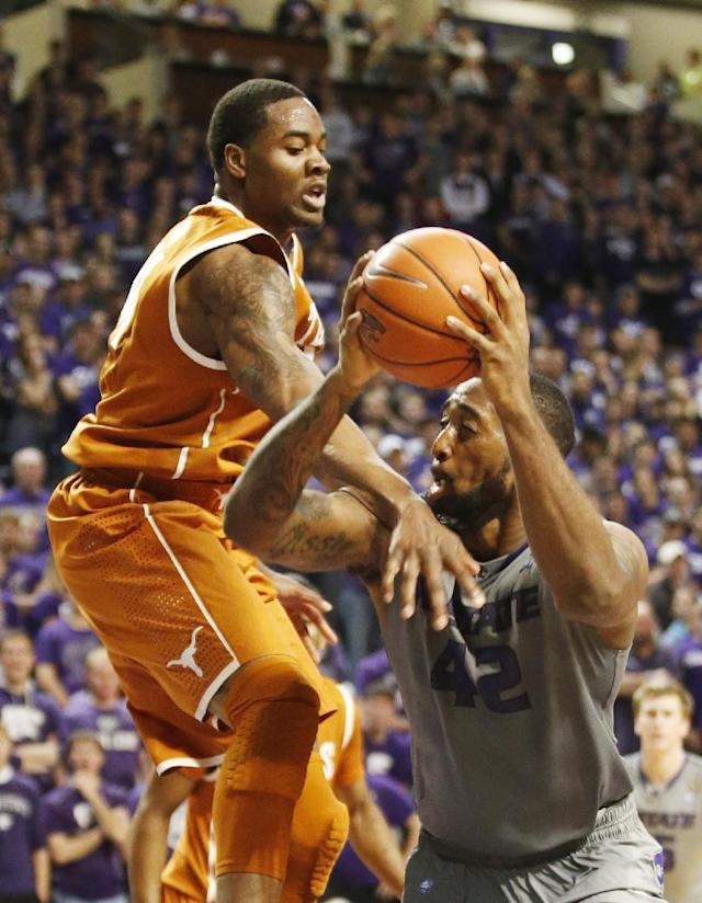 Texas center Prince Ibeh (44) fouls Kansas State forward Thomas Gipson (42) under the basket as Gipson was driving to shoot during an NCAA college basketball game Saturday, Feb. 8, 2014, in Manhattan, Kan. (AP Photo/The Wichita Eagle, Bo Rader)