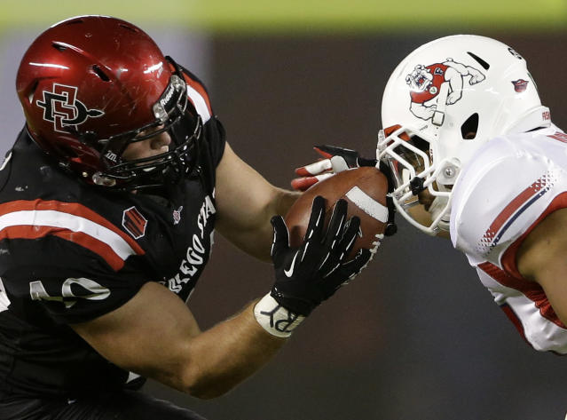 San Diego State fullback Chad Young, left, hauls in a pass off the facemask of Fresno State linebacker Kyrie Wilson, right, during the first half in an NCAA college football game Saturday, Oct. 26, 2013, in San Diego. (AP Photo/Gregory Bull)