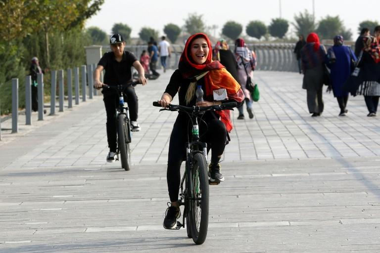 An Iranian woman rides a bicycle around the artificial Chitgar lake in Tehran, a city notorious for its traffic jams and smog