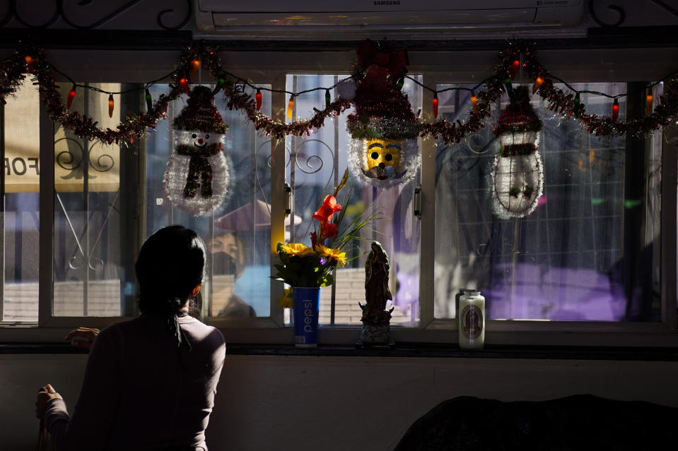 "Debbie Briano, a fourth-generation owner of Mexican restaurant, El Rancho Grande, looks at her Christmas decorations in her restaurant on Olvera Street in downtown Los Angeles, Wednesday, Dec. 16, 2020. Briano still decorated her cafe like she normally would at Christmas. She bought poinsettias, put up a real tree, hung tinsel, lights, and strung little snowmen and Santa Claus above her window. ""I had to do that to feel normal,"" she said. ""I' m not going to let COVID take away our Christmas magic."" (AP Photo/Jae C. Hong)"