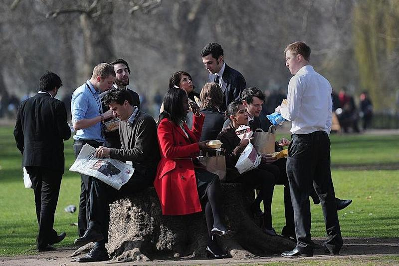 Workers share a tree stump as they eat lunch in Hyde Park: AFP/Getty Images