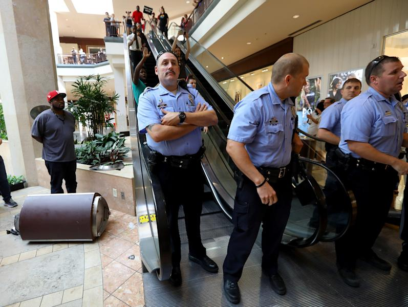 Police prevent a group of protesters from joining others on the second floor of the St. Louis Galleria mall in Richmond Heights, Mo., after a trash can was overturned during a demonstration in protest over the recent acquittal of a white former officer in the killing of a black suspect, in St. Louis, Saturday, Sept. 23, 2017. Several people were arrested at the upscale Galleria mall where demonstrators marched and chanted among shoppers. The St. Louis Post-Dispatch reported officers briefly cleared the mall after some members of the group became unruly. (Christian Goode/St. Louis Post-Dispatch via AP)