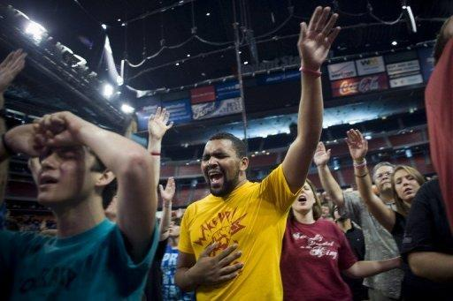 """Cody Walsh, 18, (L) and Eric Hoglund, 21, sing during the opening musical act of the non-denominational prayer and fasting event, entitled """"The Response"""" at Reliant Stadium in Houston, Texas. Texas Governor Rick Perry, expected to launch a 2012 White House bid soon, rallied the faithful for a day of Christian prayer and fasting Saturday asking God to fix America's woes"""