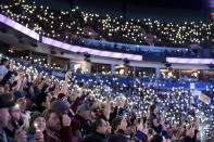 Spectators hold up cell phones with their flashlights turned on in support of those battling cancer, before the Vancouver Canucks and Colorado Avalanche played in an NHL hockey game Saturday, Nov. 16, 2019, in Vancouver, British Columbia. (Darryl Dyck/The Canadian Press via AP)