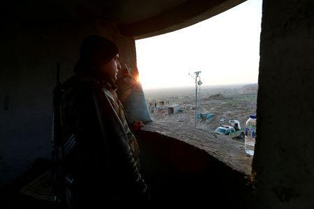 FILE PHOTO: A Popular Mobilisation Forces (PMF) fighter takes his position near the Iraqi-Syrian border in al-Qaim, Iraq, November 25, 2018. Picture taken November 25, 2018. REUTERS/Alaa al-Marjani/File Photo