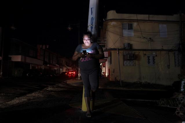 A woman uses her cell phone on a San Juan, Puerto Rico, street during a blackout on Sept. 25. (Alvin Baez/Reuters)