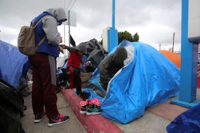 An asylum-seeking migrant talks to her children at an encampment of Mexican and Central American migrants, at El Chaparral crossing port with the U.S., in Tijuana