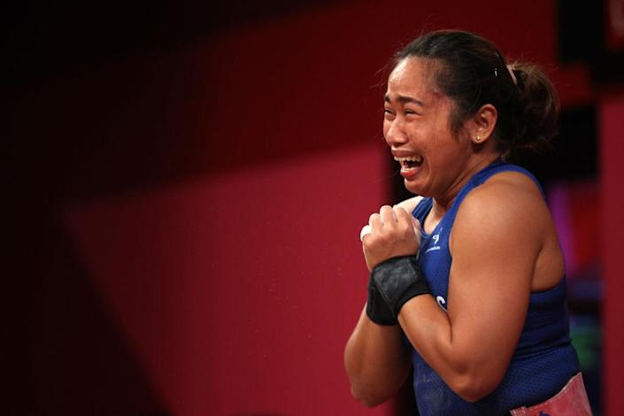 """Hidilyn Diaz of Team Philippines competes during the women's weight lifting 55kg competition on day three of the Tokyo 2020 Olympic Games at Tokyo International Forum on July 26, 2021 in Tokyo, Japan.<span class=""""copyright"""">Chris Graythen—Getty Images</span>"""