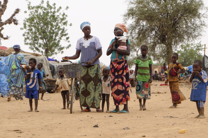 Women and children walk in a makeshift site for displaced people in Kongoussi, Burkina Faso Thursday, June 4, 2020. Jihadist violence has dramatically escalated in Burkina Faso in recent years. The country's military has struggled to contain the violence. (AP Photo/Sam Mednick)