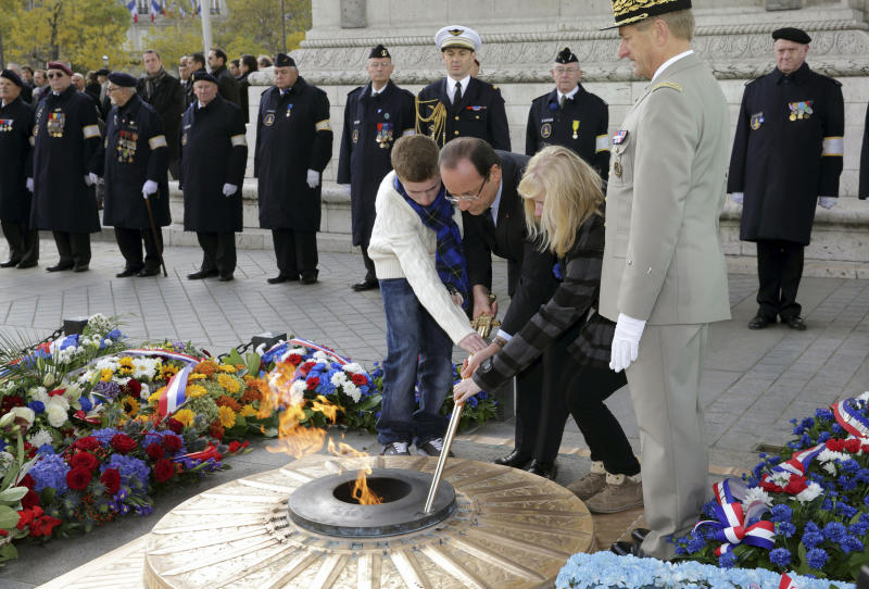 French President Francois Hollande, centre lights a flame, with the unidentified children of soldiers killed in Afghanistan, during the Armistice Day ceremony, in Paris, Sunday, Nov. 11, 2012. President Francois Hollande reviewed troops around Paris' iconic Arc de Triomphe and laid a wreath on the tomb of the unknown solider beneath the arch to commemorate France's war dead. Nov. 11 marks the signing of the truce that ended the fighting in World War I and had previously been reserved for remembering the more than 1 million French soldiers killed in that war. Hollande was accompanied Sunday by the children of soldiers who were killed in Afghanistan — a nod to the country's decision last year to commemorate all of its war dead on Armistice Day. (AP Photo/Michel Spingler, Pool)