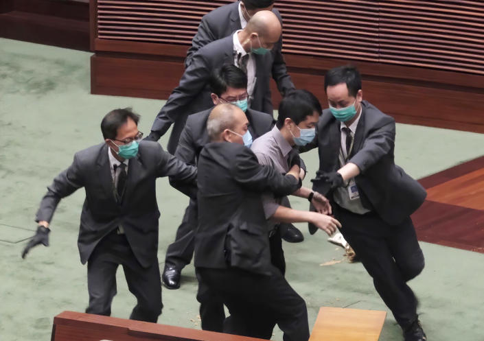 FILE - In this May 28, 2020, file photo Pro-democracy lawmaker Ted Hui, center, struggles with security personnel at the main chamber of the Legislative Council during the second day of debate on a bill that would criminalize insulting or abusing the Chinese anthem in Hong Kong. Former Hong Kong pro-democracy lawmaker and activist Ted Hui Chi-fung said, Wednesday, March 10, 2021, he had relocated to Australia where he would continue campaigning against the Chinese Communist Party. (AP Photo, FILE)