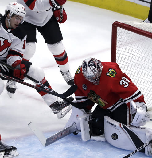 Chicago Blackhawks goalie Cam Ward, right, blocks a shot by New Jersey Devils center Nico Hischier during the first period of an NHL hockey game Thursday, Feb. 14, 2019, in Chicago. (AP Photo/Nam Y. Huh)
