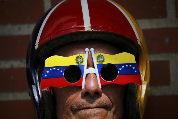An anti-government protester wears Venezuelan flag motif sunglasses during a demonstration demanding the resignation of President Nicolas Maduro, in Caracas, Venezuela, Saturday, Feb. 2, 2019. Momentum is growing for Venezuela's opposition movement led by self-declared interim president Juan Guaido, who has called supporters back into the streets for nationwide protests Saturday, escalating pressure on Maduro to step down. (AP Photo/Fernando Llano)