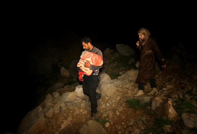 In this picture taken late Saturday April 19, 2014, a Syrian man carries his newborn baby in his arms, left, as he and his wife, right, descend a mountain path from the 2,814-meter (9,232-foot) high Mount Hermon (Jabal el-Sheikh), into the town of Chebaa in southeast Lebanon. Violence forced them to flee their home in the Syrian village of Beit Jinn, near the Israeli-occupied Golan Heights. The group of Syrians that reached Chebaa at sunrise on Sunday joined more than 1 million other Syrian refugees inside Lebanon. (AP Photo/Hussein Malla)