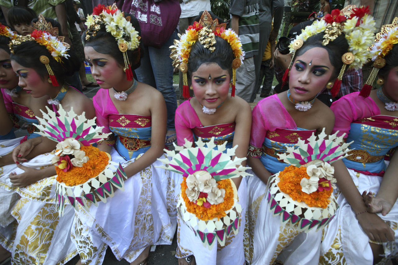 Balinese girls wear traditional dresses during a parade a day before Nyepi, the annual day of silence marking the Balinese Hindu New Year in Denpasar, Bali, Indonesia, Thursday, March 22, 2012. Hindus in the world's most populous Muslim country will celebrate their new year Friday by observing a day of silence in which they have to stay inside their homes and meditate in silence and darkness for the entire day.  (AP Photo/Firdia Lisnawati)