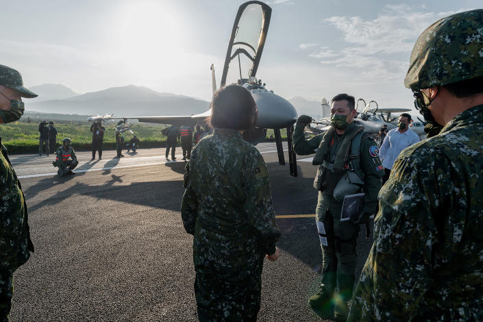 In this photo released by the Taiwan Presidential Office, Taiwanese President Tsai Ing-wen, center, speaks with military personnel near aircraft parked on a highway in Jiadong, Taiwan, Wednesday, Sept. 15, 2021. Four military aircraft landed on the highway and took off again on Wednesday as part of Taiwan's five-day Han Guang military exercise designed to prepare the island's forces for an attack by China, which claims Taiwan as part of its own territory. (Taiwan Presidential Office via AP)
