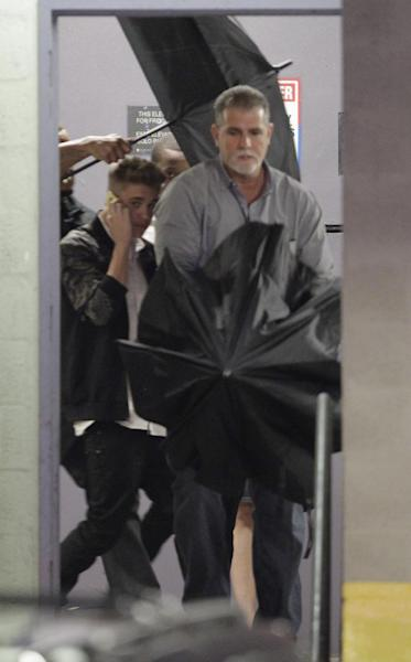 Justin Bieber , left, leaves his lawyers office in Miami, Thursday, March 6, 2014, after testifying in a civil deposition regarding an alleged assault on a photographer last year. (AP Photo/Luis M. Alvarez)
