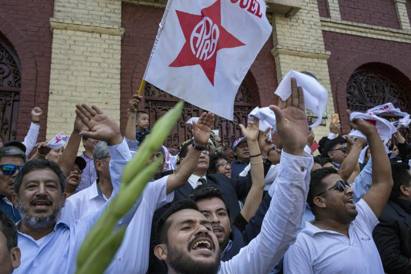 Supporters of Peru's late President Alan Garcia chant slogans during his funeral procession in Lima, Peru, Friday, April 19, 2019. Garcia shot himself in the head and died Wednesday as officers waited to arrest him in a massive graft probe that has put the country's most prominent politicians behind bars and provoked a reckoning over corruption. (AP Photo/Rodrigo Abd)