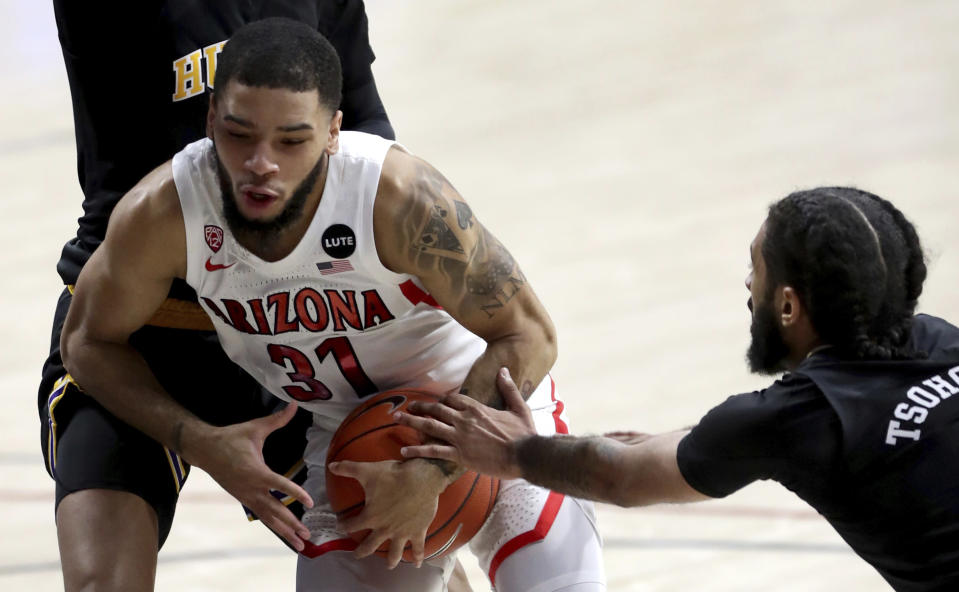 Washington guard Marcus Tsohonis (0) gets a handful of Arizona guard Terrell Brown Jr. (31) as he penetrates the lane in the first half of an NCAA college basketball game Saturday, Feb. 27, 2021, in Tucson, Ariz. (Kelly Presnell/Arizona Daily Star via AP)