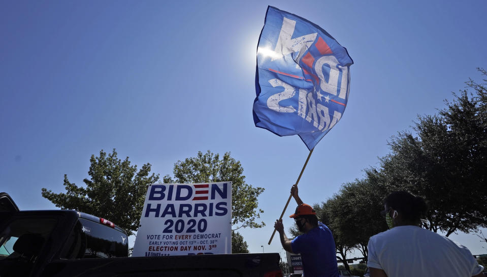 A supporter of Democratic presidential candidate former Vice President Joe Biden places a flag on a pick-up truck bed in for a Ridin' With Biden event Sunday, Oct. 11, 2020, in Plano, Texas. Democrats in Texas are pressing Joe Biden to make a harder run at Texas with less than three weeks until Election Day. (AP Photo/LM Otero)