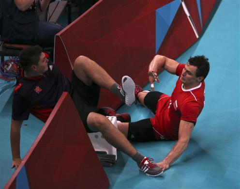 Poland's Zbigniew Bartman (R) crashes into a ball boy as he chases the ball during their men's Group A volleyball match against Bulgaria at the London 2012 Olympic Games at Earls Court July 31, 2012.