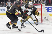 Vegas Golden Knights right wing Ryan Reaves (75) and Minnesota Wild center Nico Sturm (7) compete for the puck during the first period of Game 2 of a first-round NHL hockey playoff series Tuesday, May 18, 2021, in Las Vegas. (AP Photo/David Becker)