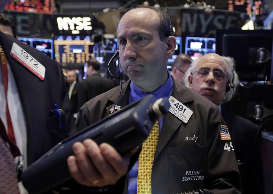 Trader Andrew Silverman, center, works on the floor of the New York Stock Exchange, Thursday, Dec. 12, 2013. Lower U.S. stock prices on Thursday set up investors for what would be their third day in a row of declines. (AP Photo/Richard Drew)