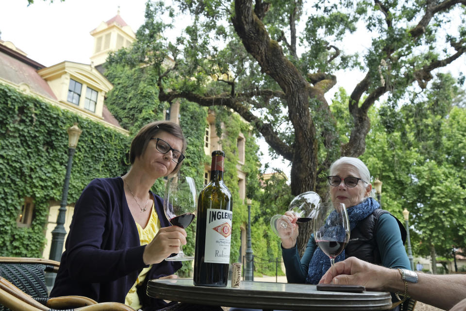 Shana Ayers, left, of Kansas City, Mo., Susan Goodwin, of Fresno, Calif., taste the 2016 Rubicon at the Inglenook winery Friday, June 12, 2020, in Rutherford, Calif. California wineries started uncorking their bottles and welcoming people back to their tasting rooms Friday as the state's $145 billion tourism industry gears up with hotels, zoos, museums and aquariums also allowed to reopen. The historic winery, which dates to 1879, reopened Friday to wine club members after being closed since mid March because of the coronavirus threat and will be open to the public on June 25. (AP Photo/Eric Risberg)