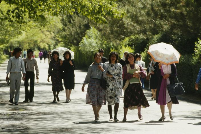 Young men and women stroll in Kabul park.