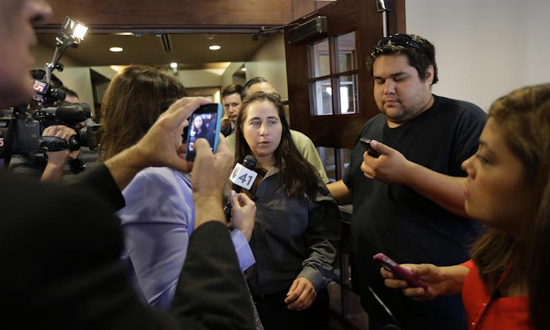 Anna Vasquez, center, walks past members of the media as she leaves a courtroom at the Bexar County Courthouse, Monday, Nov. 18, 2013, in San Antonio, after it was announced that three of four San Antonio women imprisoned for sexually assaulting two girls in 1994 were expected to walk free after a judge agreed that their convictions were tainted by faulty witness testimony. Vasquez, the fourth woman, has already been paroled, but under strict conditions. (AP Photo/Eric Gay)
