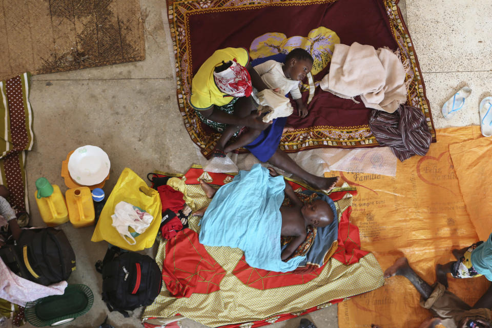 FILE - In this file photo dated Monday, April, 29, 2019, a mother and her children prepare for the night inside a Roman Catholic Church in Pemba city on the northeastern coast of Mozambique. Northern Mozambique's humanitarian crisis is quickly growing, with more than 650,000 people displaced by the Islamic extremist insurgency in the Cabo Delgado province, and nearly 1 million people in need of humanitarian aid, according to international aid groups, Tuesday March 16, 2021. (AP Photo/Tsvangirayi Mukwazhi, FILE)
