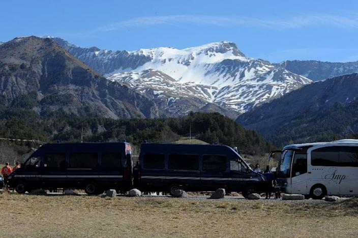 Gendarmerie vans block the view as relatives of Japanese victims pay their respects on March 29 2015 near a commemorative headstone in Seyne-les-Alpes (AFP Photo/Jean-Pierre Clatot)
