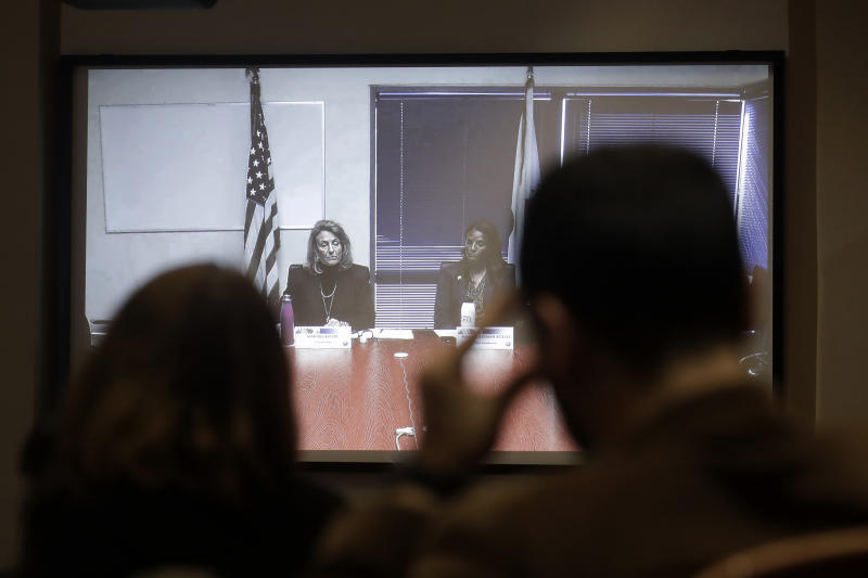 California Public Utilities Commission President Marybel Batjer, from left on video screen, and Commissioner Martha Guzman speak during a CPUC meeting in San Francisco, Wednesday, Nov. 13, 2019. California regulators will vote Wednesday on whether to open an investigation into pre-emptive power outages that blacked out large parts of the state for much of October as strong winds sparked fears of wildfires.  (AP Photo/Jeff Chiu)
