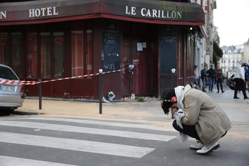 A woman mourns outside of the Carillon bar in the 10th district of Paris, on November 14, 2015