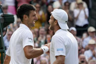 Serbia's Novak Djokovic shakes hands with Denis Kudla of the US, right, after winning the men's singles third round match on day five of the Wimbledon Tennis Championships in London, Friday July 2, 2021. (AP Photo/Alberto Pezzali)