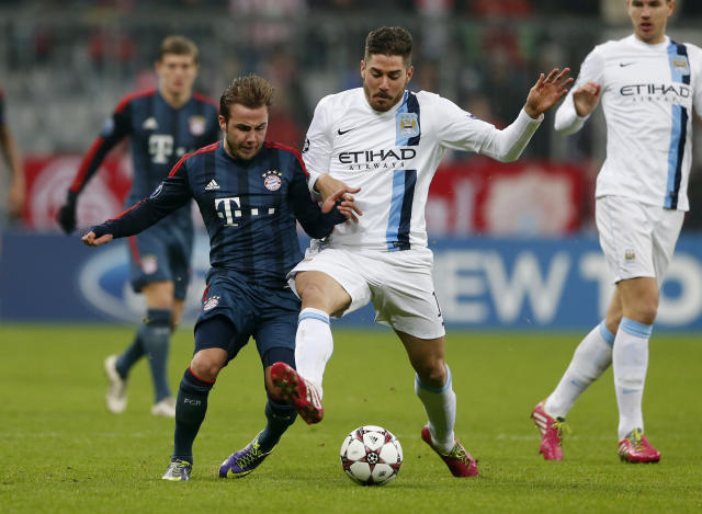 Bayern's Mario Goetze, left, and Manchester City's Javi Garcia challenge for the ball during the Champions League group D soccer match between FC Bayern Munich and Manchester City, in Munich, southern Germany, Tuesday, Dec. 10, 2013. (AP Photo/Matthias Schrader)