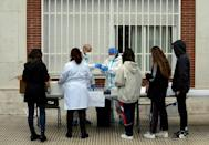 Health personnel collect saliva samples from pupils in a school in Madrid on December 17, 2020 for a study on coronavirus transmission between children and from children to adults