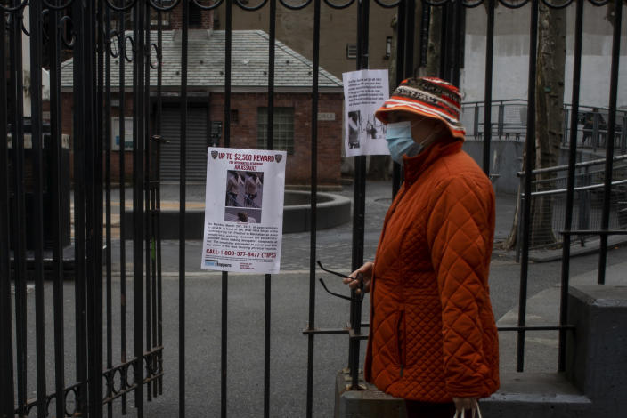 A woman in Manhattan on March 31, 2021, walks past a police flyer advertising a reward for information about the assault on a Filipino woman in midtown. (Andrew Seng/The New York Times)
